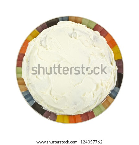 Looking down at a frosted layer cake on a colorful plate. - stock photo