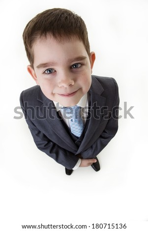 looking down at a happy small boy dressed up as a business person