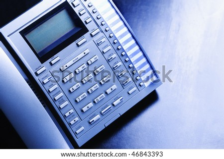 Looking down at a multi-line business telephone sitting on a desk. Horizontal shot. - stock photo