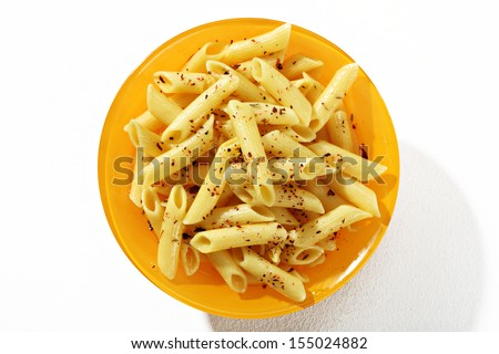Looking down at a plate of cooked penne pasta with spices / top view of spiced macaroni noodles in an orange plate  - stock photo