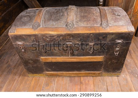 Looking Down at Old Dusty Antique Treasure Chest with Rusty Iron Accents and Key in Lock on Deck of Sailing Ship - stock photo