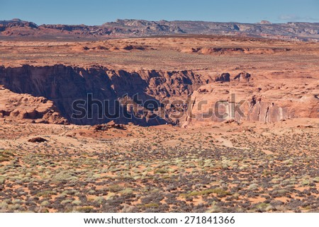 Looking down at tourist standing on the edge of Glen Canyon at Horseshoe Bend gives the perspective of the enormity of the canyon. - stock photo