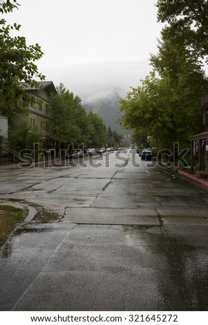 Looking down Millward Street to Snow King ski area, downtown Jackson, Wyoming, on a rainy summer day, with shiny wet roads, vertical image. - stock photo