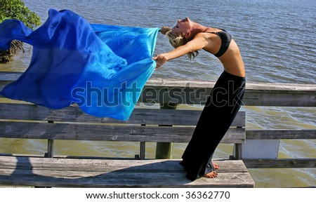looking down on a beautiful fit young woman as she does a yoga stretch on a dock facing the sun with blue silk cloth flowing out behind her. - stock photo