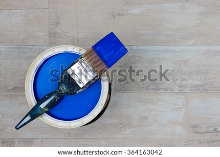 Looking down on a can of Dark Blue Paint with a loaded brush stood on a shabby style wood floor - stock photo