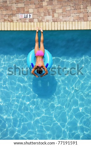 Looking down on a girl suntanning in a swimming poo on a pool float / pool ring, room for your text - stock photo