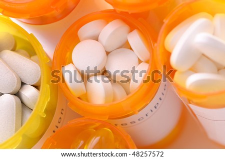 Looking down on a group of open prescription bottles with assorted pills closeup horizontal composition shallow depth of field - stock photo