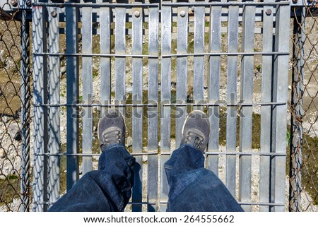 Looking down on a suspension bridge over a river in Nepal - stock photo