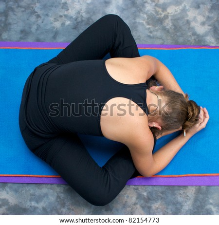 Looking down on an athletic brown haired woman doing yoga exercise Bound Angle Forward Bend pose on yoga mat in studio with mottled background.
