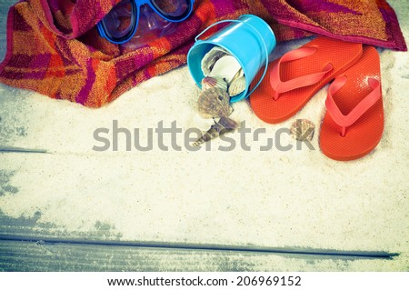 Looking down on Beach Still Life.  Towel, Bucket, Seashells, Orange Rubber Sandals, Swim Mask.  Room or space for copy, text, words rustic board walk sand background.  Horizontal vintage, instagram. - stock photo
