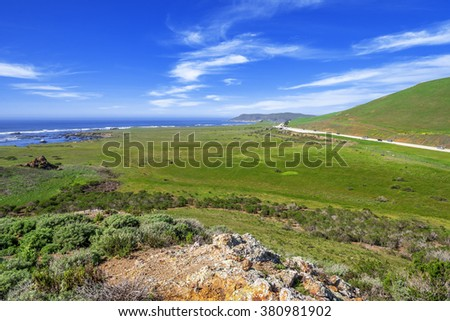 Looking down on Highway 1 & Estero Bluffs state park, you see blue seas & skies, white clouds, green hills, hiking, walking, trails & Point Estero. Near the seaside village of Cayucos & Morro Bay, CA. - stock photo