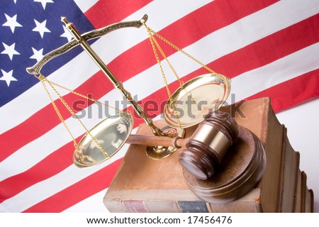 Looking down on scales of justice, gavel, and stack of old law books in front of American Flag - stock photo