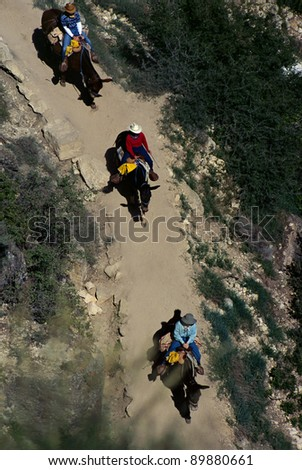 Looking down on three riders in the Grand Canyon, USA - stock photo