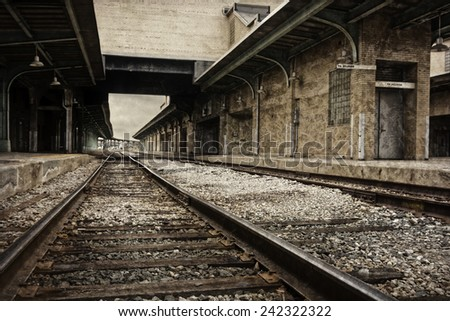 Looking down the rustic ruins of railroad tracks of an old train station depot processed in a sepia tone.  - stock photo