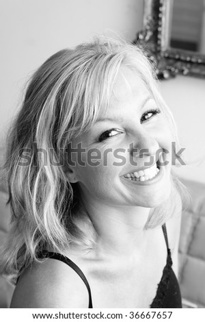 looking down towards a beautiful blonde woman that is looking at viewer and laughing , black and white image - stock photo