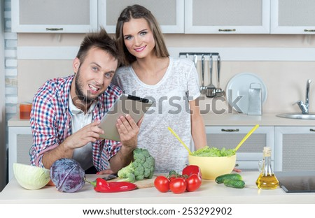 Looking for ideal food recipe. Young and beautiful couple in love is preparing food on the kitchen, while looking for a recipe in tablet