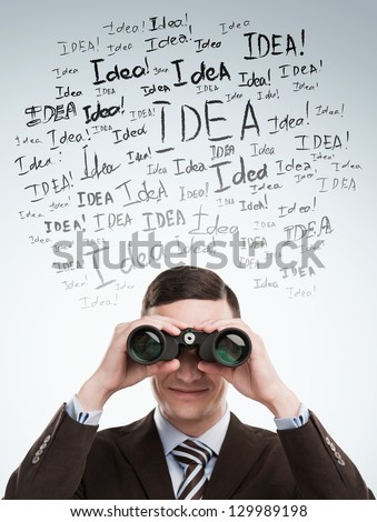 Looking for Ideas concept. Young business man standing on gray background with with binoculars idea signs in front