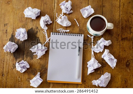 Looking for ideas, writing work. Composition of crumpled papers, notebook, pen and tea at wooden table. - stock photo
