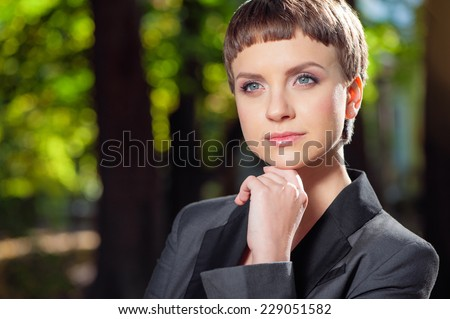 Looking for inspiration. Close up portrait of Confident Thoughtful caucasian young business woman in formalwear holding hand on chin and looking away while standing outdoors - stock photo