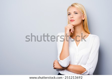 Looking for inspiration. Thoughtful young women holding hand on chin while standing against grey background - stock photo
