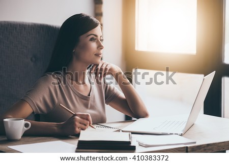 Looking for inspiration. Young beautiful pensive woman making some notes and looking through window while sitting in chair at her working place - stock photo