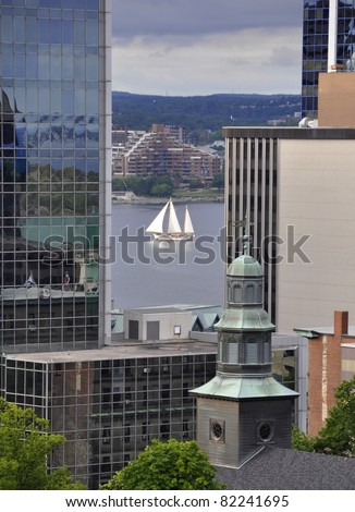 looking from the past the tall buildings of downtown Halifax towards the harbor, Tallship sailing by in between the buildings; Halifax Nova Scotia Canada - stock photo