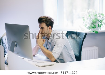 Looking from the working men in the office. Stylish designer at work sitting at a desk. Focused on his job businessman looking at computer. White interior