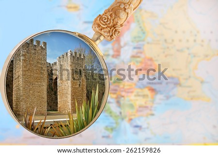 Looking in on Entrace into old town of Lagos, Algarve, Portugal with a magnifying glass or loop with European map in the background - stock photo