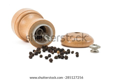 looking inside a small wooden pepper mill. - stock photo