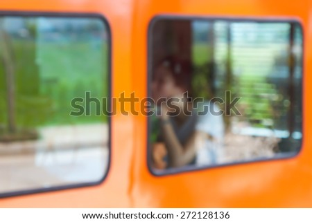 Looking into the cafe with a glass and a woman sitting in a blurred image is not clear tone of the background - stock photo