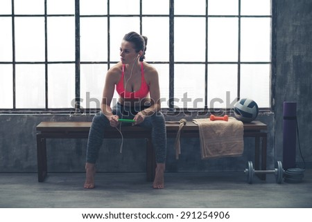 Looking off to the side, an athletic woman watches something in the distance. She is sitting on a bench by a window in a loft gym, holding her device and listening to music.
