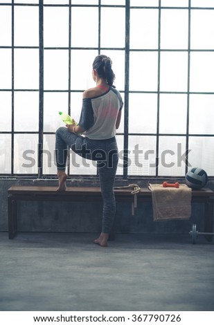 Looking out at the buzz of the city below, a woman stands gently stretching out her leg on a bench, holding a bottle of water in one hand while she rests it against her knee. - stock photo