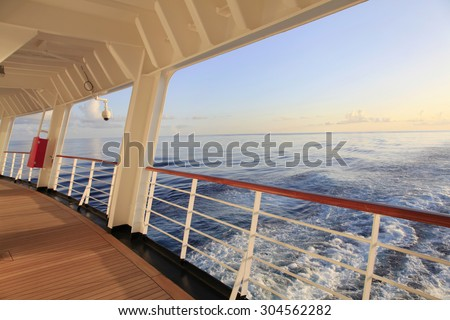 Looking Out Over the Stern of a Cruise Ship as the Sun Sets - stock photo