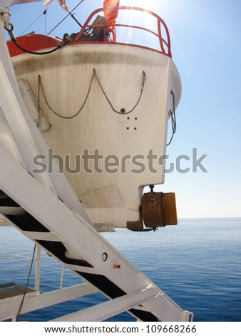 Looking out to sea from the deck of a cruise ship past the stern and propellor of a lifeboat suspended on a davit - stock photo