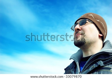 Looking out to the future (man in the blue sky) - stock photo