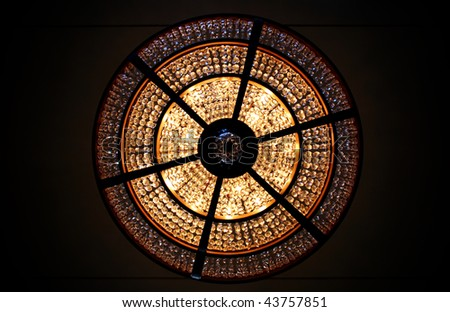 Looking straight up at a lit chandelier - stock photo