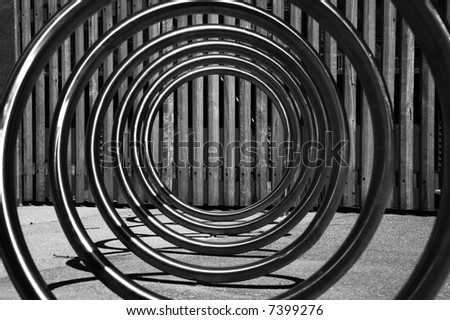 looking through a steel bicycle rack in b&w