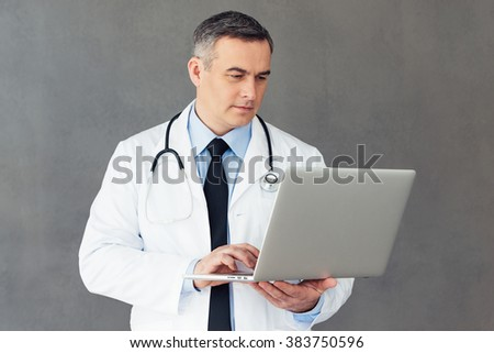 Looking through medical results. Mature male doctor using his laptop while standing against grey background - stock photo