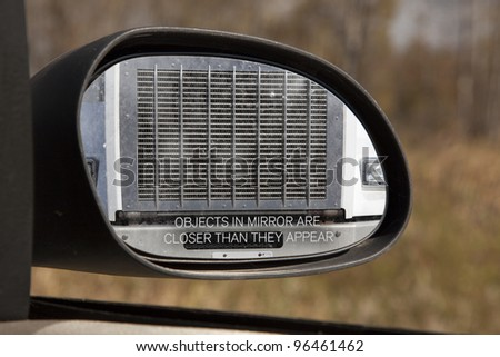 Looking through the rear view mirror you see the front grill of a large truck, obviously too close for comfort. - stock photo
