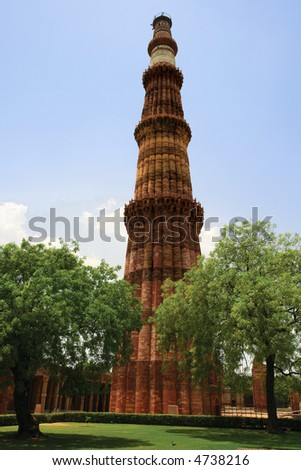 Looking through the trees at Qutub Minar, the red sandstone tower in Delhi, India. - stock photo