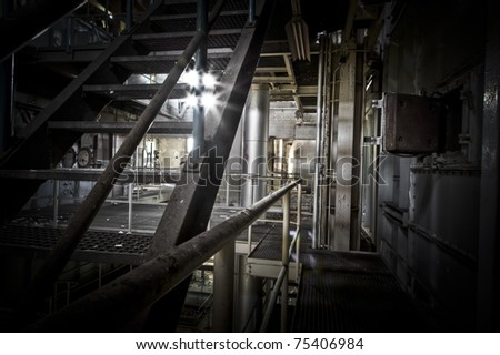 Looking trough the stairs at this abandoned power station, light shines trough as if its for the last time. - stock photo