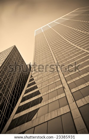 Looking up a curved skyscraper office blockn sepia tone - stock photo