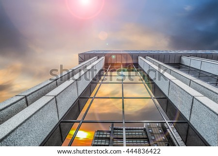 Looking up at a building with colourful sky and sun glare - stock photo