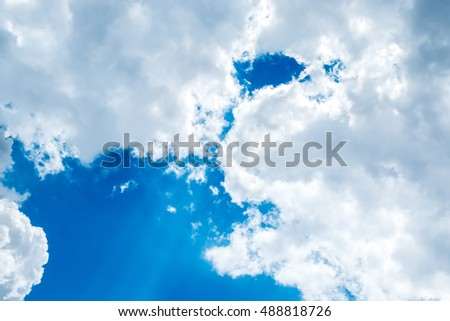 Looking up at Big white cloud and light ray behind cloud with blue sky.