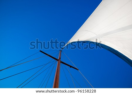 Looking up at mast of boat to blue sky - stock photo