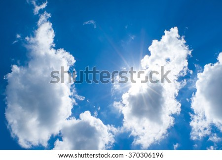Looking up at Nice blue sky with sun beam behind big cloud - stock photo