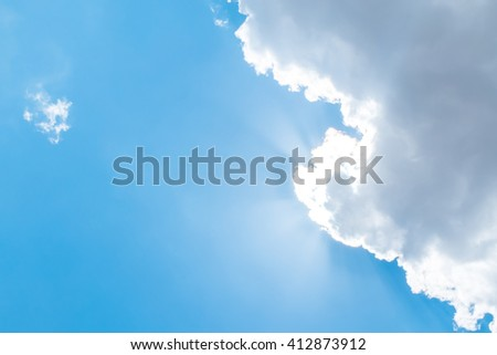 Looking up at Nice blue sky with sun beam behind big cloud.