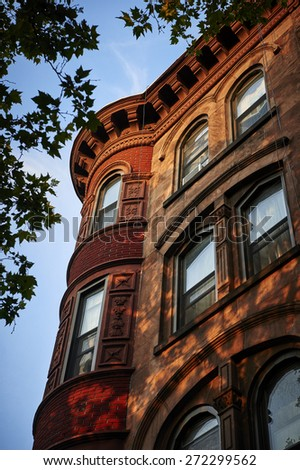 looking up at the corner of a brownstone building - stock photo