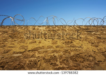 Looking up at the razor wire on top of a stone prison wall. - stock photo