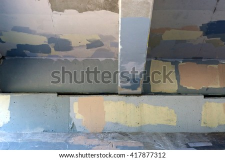 Looking up at the underside of a bridge that has had graffiti painted over in various colors of paint making an interesting background. - stock photo